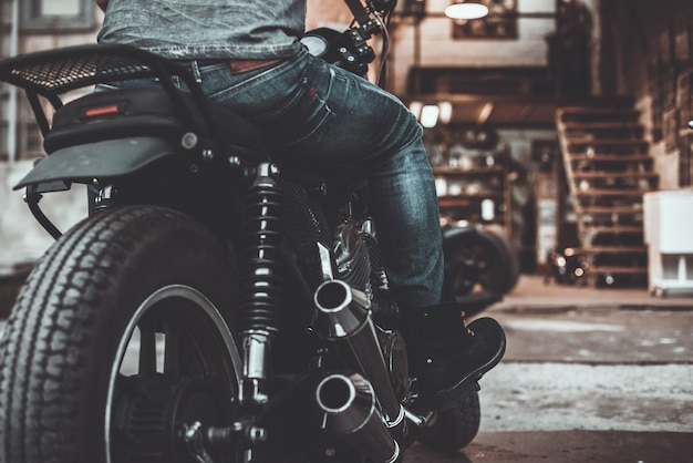 On the way to his garage. close-up rear view of man sitting on his bike with motorcycle garage in the background