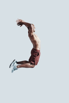 On the way to success. full length of young african man in sport clothing making a face while jumping against grey background