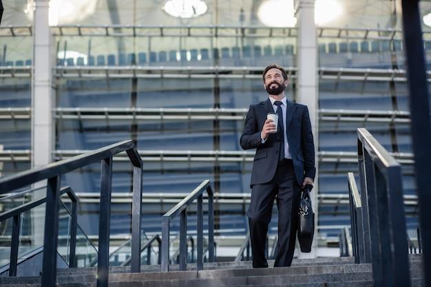 ビジネスミーティングへの道。階段を歩きながらコーヒーを飲むプロのビジネスマン