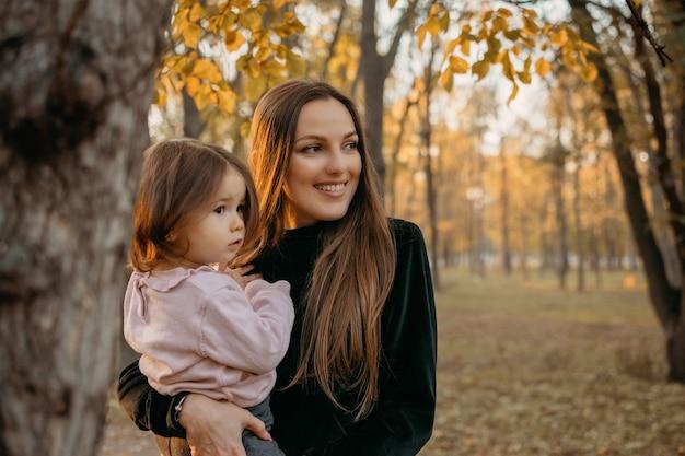 Способы нести малыша крупным планом на открытом воздухе портрет счастливой семейной мамы и девочки-малыша осенью