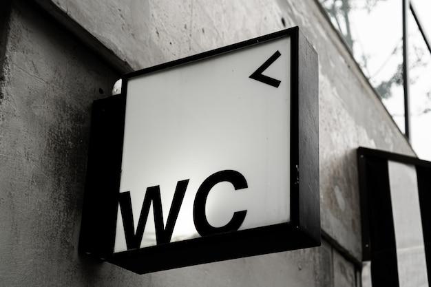 흑백 스타일 콘크리트 벽에 부착 된 화장실 표시