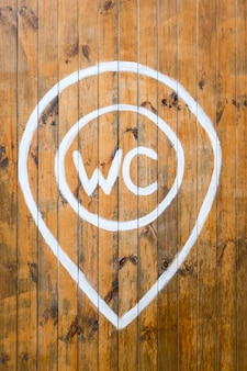 Wc sign with white painted text on wooden wall.