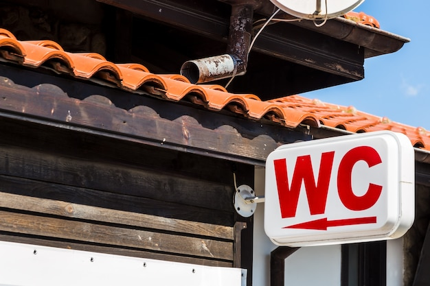 Wc signboard with direction arrow fixed on the building