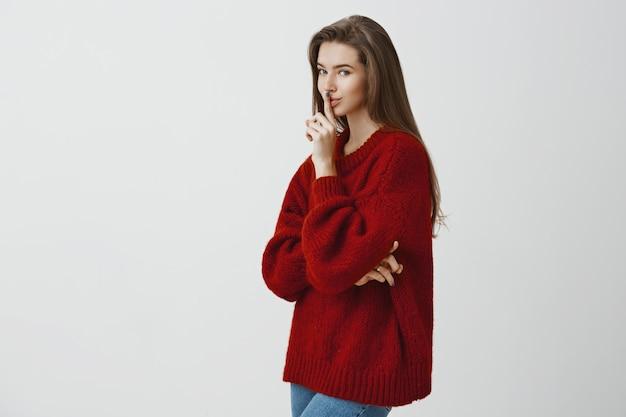 Tutti abbiamo segreti negli armadi. ritratto di romantica donna europea sensuale in maglione rosso sciolto, in piedi nel profilo, dicendo zitto o zitto gesto, nascondendo qualcosa sul muro grigio