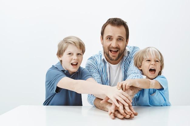 私たちはこれを一緒にしています。楽しい瞬間を共有する幸せな遊び心のある家族の肖像画