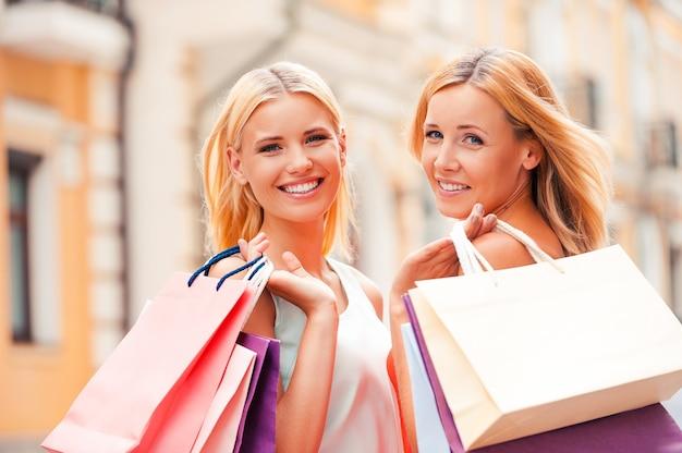 우리는 항상 함께 쇼핑을 갑니다. 쾌활한 성숙한 여성과 그녀의 딸이 쇼핑백을 들고 야외에서 걷는 동안 카메라를 보고 있습니다.