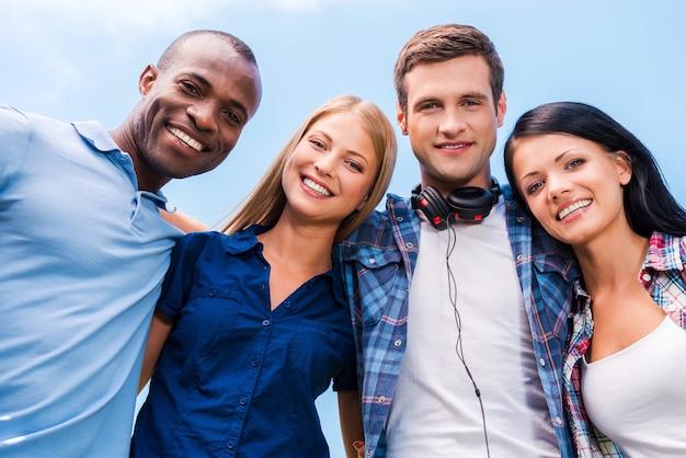 우리는 모두 좋은 친구입니다. 푸른 하늘을 배경으로 미소를 지으며 카메라를 바라보며 유대감을 형성하는 4명의 행복한 젊은 사람들의 낮은 각도 보기