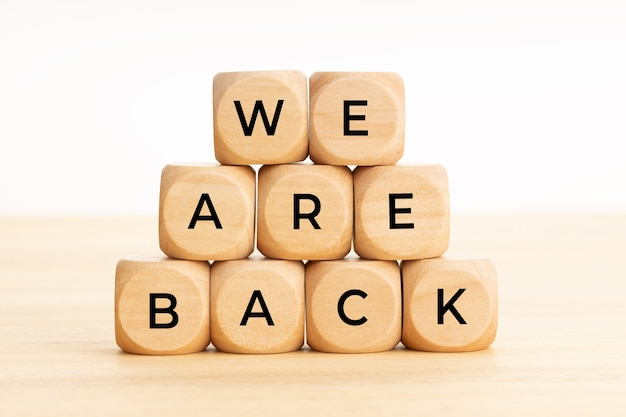 We are back words on wooden blocks on table