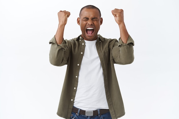 We are champions. portrait of triumphing african-american man celebrating victory, fist pump, feel empowered and happy, shouting yes