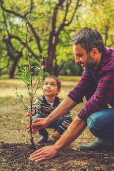 우리는 모든 것을 함께하고 있습니다. 그의 어린 아들이 그를 돕는 동안 나무를 심는 행복한 청년