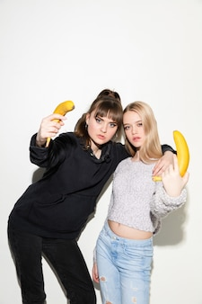 We are friends. close up fashion portrait of two young cool hipster girls wearing jeans wear.  two models having fun and making serious faces.