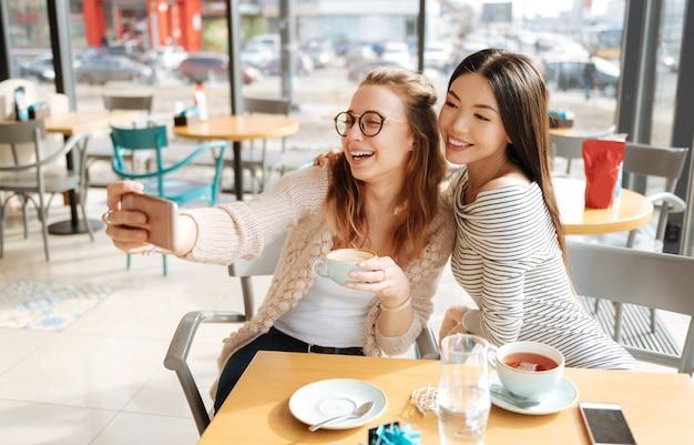 우린 행복해. 미소하고 카페에 앉아있는 동안 함께 사진을 찍는 두 어린 소녀의 멋진 초상화.