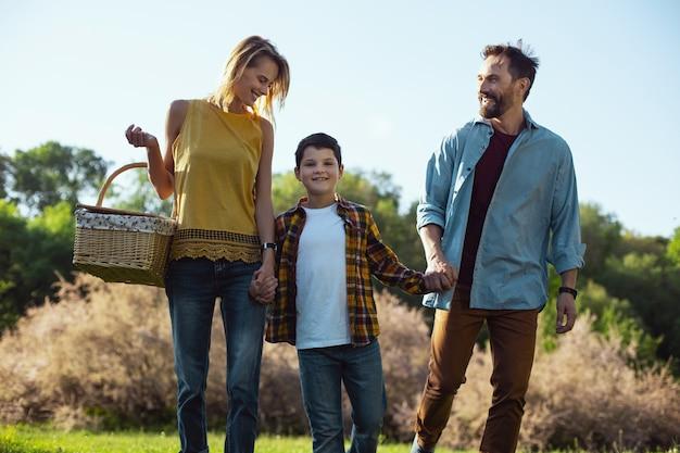 우린 행복해. 바구니를 들고 그녀의 가족과 함께 산책하는 데 금발 어머니 미소