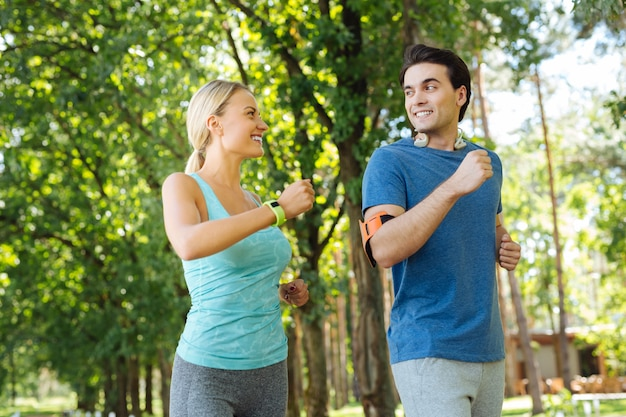 We are healthy. delighted nice couple smiling while doing sports activities together