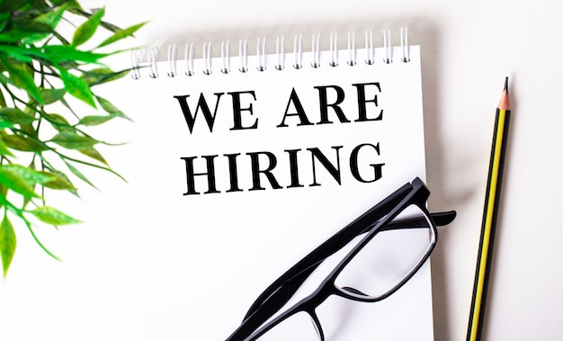 We are hiring is written in a white notebook next to a pencil, black-framed glasses and a green plant