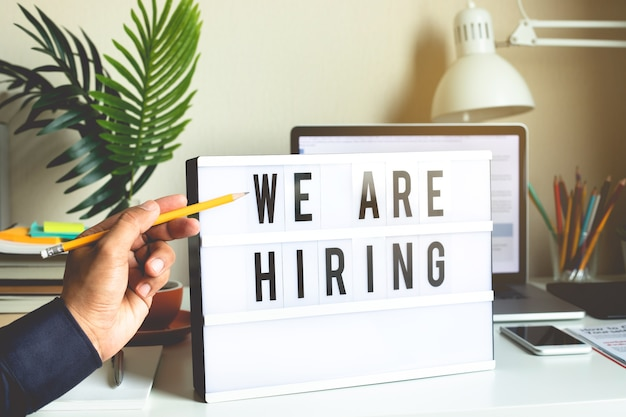 We are hiring text on light box on desk office.