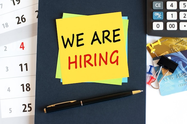 We are hiring - text on yellow paper on blue background, concept
