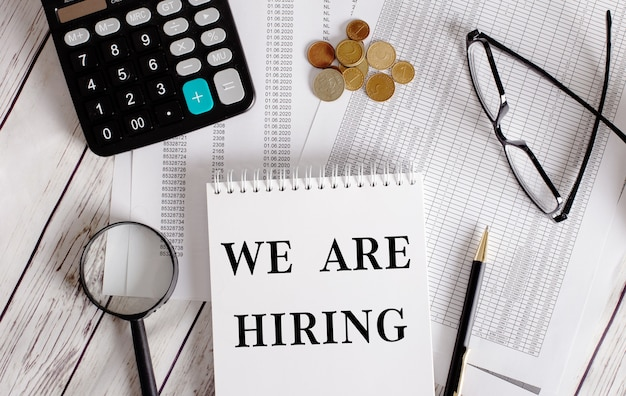 We are hiring written in a white notepad near a calculator, cash, glasses, a magnifying glass and a pen. business concept