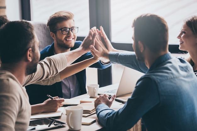 私たちは市場のリーダーです!ビジネスミーティングでオフィスのテーブルに座って笑顔でハイタッチをしている陽気な若者