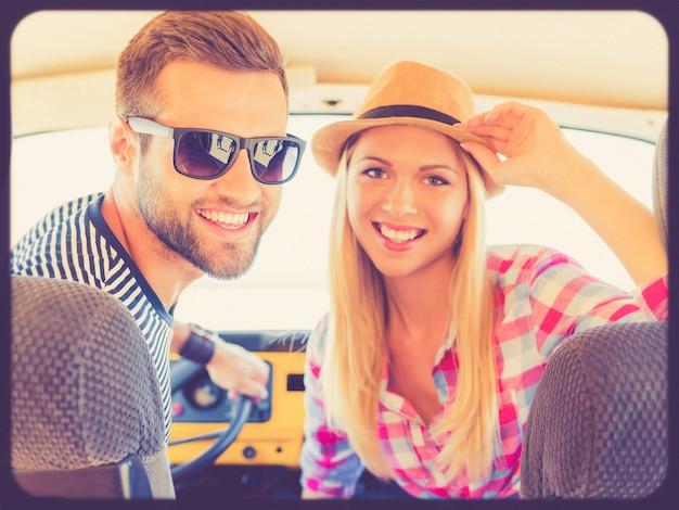 Ищем приключений. веселая молодая пара улыбается и смотрит в камеру, сидя в машине