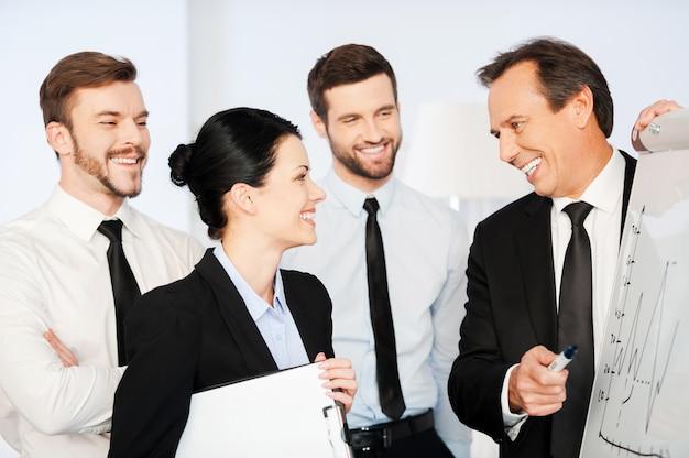 Мы делаем большие успехи! уверенный зрелый бизнесмен, указывая график на доске и улыбаясь, пока его коллеги стояли рядом с ним