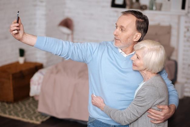 私たちは現代的です。妻を抱きしめて、家に立って自分撮りをしているハンサムな老人の肖像画。