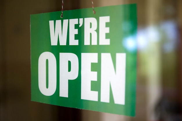We are open sign on the glass of the door at store