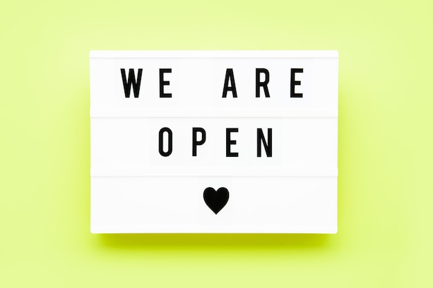 We are open written in light box on green background. end of quarantine concept. copy space, top view
