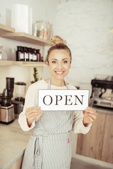 Мы открыты. красивая улыбающаяся владелица стартапа приветствует гостей своего нового кафе.