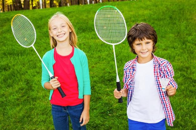 プレイする準備ができました!バドミントンラケットを持って、一緒に緑の芝生の上に立って笑っている2人のかわいい小さな子供たち