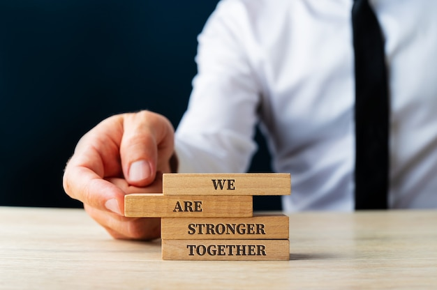 We are stronger together sign on wooden pegs being stacked by a business executive in a conceptual image.