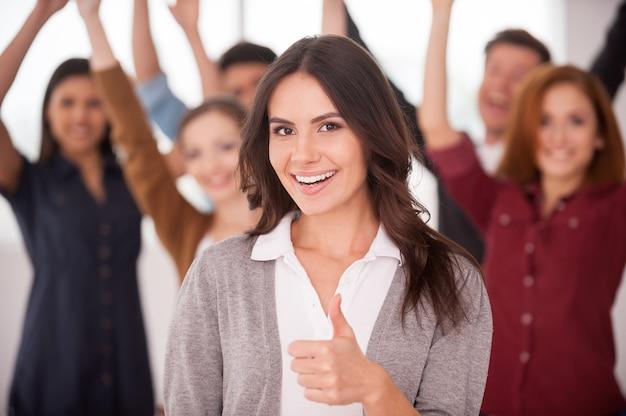 Мы успешная команда! красивая молодая женщина показывает палец вверх и улыбается, в то время как группа счастливых молодых людей стоит на фоне и держит руки