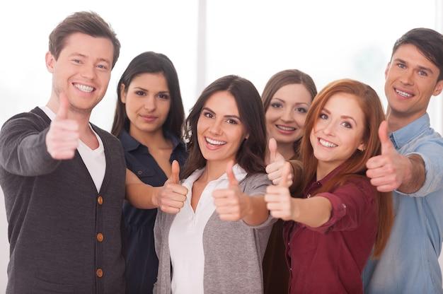 Мы успешная команда! группа веселых молодых людей, стоящих рядом и жестикулирующих