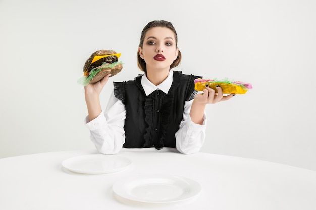 우리는 우리가 먹는 것이다. 여자는 플라스틱, 에코 개념으로 만든 햄버거와 핫도그를 먹는다