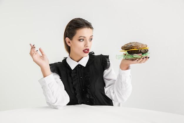 우리는 우리가 먹는 것이다. 플라스틱, 에코 개념으로 만든 여자의 먹는 햄버거