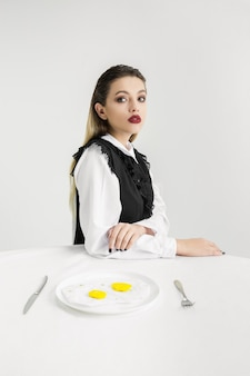 私たちは私たちが食べるものです。プラスチック製の目玉焼きを食べる女性、エココンセプト。ポリマーがたくさんあるので、私たちはそれでできています。環境災害、ファッション、美容、食品。有機的な世界を失う。