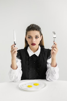 Мы - то, что мы едим. женщина ест яичницу из пластика, экологическая концепция. полимеров так много, что мы просто сделаны из них. экологическая катастрофа, мода, красота, еда. теряя органический мир.
