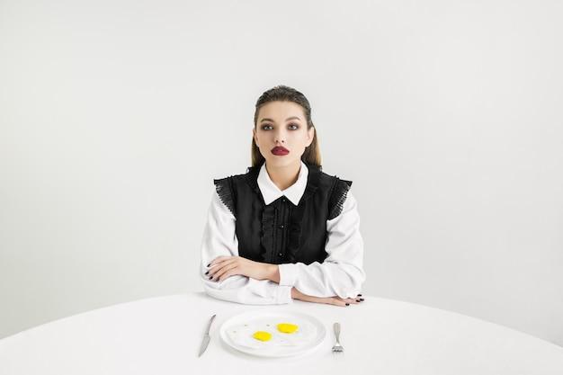 私たちは食べるものです。プラスチック製の目玉焼きを食べる女性、エココンセプト