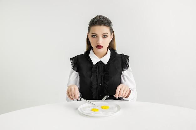 Мы - то, что мы едим. женщина ест яичницу из пластика, экологическая концепция