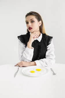We are what we eat. woman's eating fried eggs made of plastic, eco concept