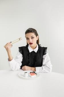 우리는 우리가 먹는 것이다. 플라스틱, 에코 개념으로 만든 여자의 먹는 초밥. 폴리머가 너무 많아서 우리는 그것으로 만들어졌습니다. 환경 재해, 패션, 미용, 음식. 유기 세계를 잃어 버리고 있습니다.