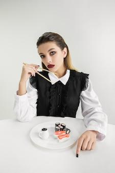 Мы - то, что мы едим. женщина ест суши из пластика, экологическая концепция. полимеров так много, что мы просто сделаны из них. экологическая катастрофа, мода, красота, еда. теряя органический мир.