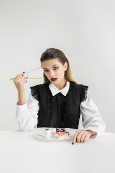 Мы - то, что мы едим. женщина ест суши из пластика, экологическая концепция Premium Фотографии