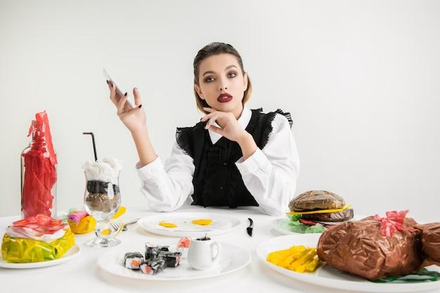 우리는 우리가 먹는 것이다. 플라스틱, 에코 개념으로 만든 요리에 대해 스마트 폰을 사용하는 여성