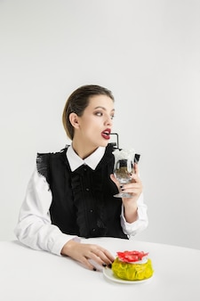 私たちは私たちが食べるものです。ドーナツを持つ女性、プラスチック製のカクテル、エココンセプト。ポリマーがたくさんあるので、私たちはそれでできています。環境災害、ファッション、美容、食品。有機的な世界を失う。