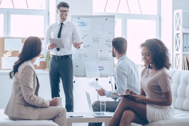 できる!デジタルタブレットを持って、オフィスに立っている間笑顔で彼の同僚と何かを話している若いハンサムな陽気な男