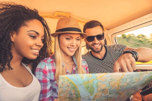 Мы можем пойти куда угодно! три радостных молодых человека изучают карту и улыбаются, сидя в своем мини-фургоне