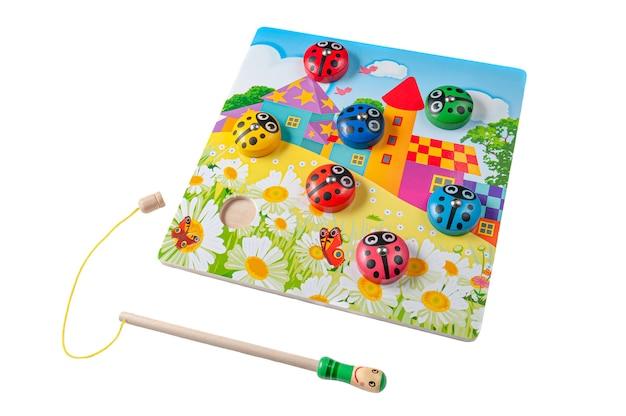 磁気棒でテントウムシを捕まえます。マテリアルツリー。教育玩具モンテッソーリ。白色の背景。閉じる。