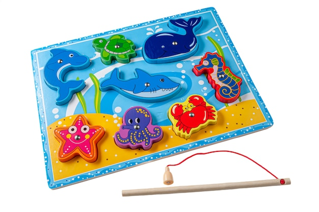 磁気ロッドで海洋生物を捕まえます。素材は木です。教育玩具モンテッソーリ。白色の背景。閉じる。