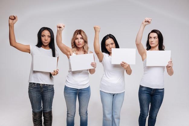 Меняем все вместе. замечательные современные страстные женщины, стоящие вместе, в одинаковой одежде и в одинаковых позах.